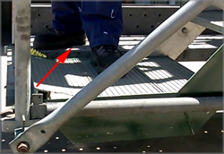 Photograph 2 – Aluminium deck peeled away (as indicated by arrow) when a worker stepped onto it and the stairs dropped.