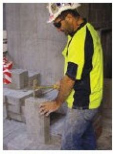 A Bricklayer splitting bricks using a hammer