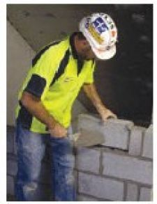 A Bricklayer laying bricks into position